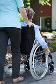 Nurse walking with elderly woman on wheelchair