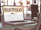 Portfolio on Laptop in Modern Workplace Background.