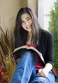 Beautiful teenage girl studying next to sunny window