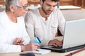 Man helping elderly family member shop on-line
