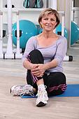 Woman sat stretching in the gym