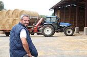 Farmer stood by hay barn