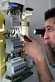 Electrician examining a fusebox with a torch