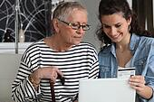 grandma and home helper with laptop