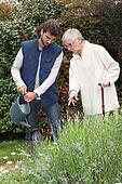 A gardener watering flowers in a garden and an elderly lady making comments as she watches him.