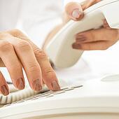 Closeup of female telephone operator dialing a phone number