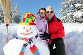grandfather wearing sunglasses posing with young granddaughter at ski near snowman
