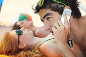 young man phoning at the beach with his friends