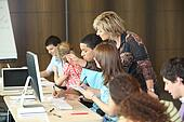 Group of students looking at a computer with a teacher