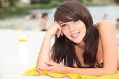 Teenage girl sunbathing on a beach