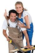 Couple stood by work bench doing home improvements