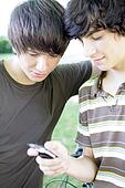 Two male teens reading text message
