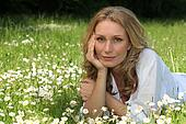 Woman laying down in field full of flowers