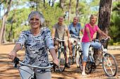 Senior woman and her friends riding bikes through the countryside