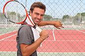 Man stood in front of tennis court holding racket over shoulder