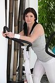 Healthy woman on cross trainer