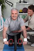 Grey haired man with personal trainer