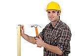 Carpenter driving a nail in a beam, studio shot