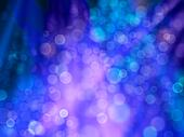 Patches and rays of light of blue and purple as celebratory background