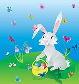 easter hare on the green grass under blue sky with eggs in basket and butterflies around