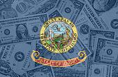 US state of idaho flag with transparent dollar banknotes in back