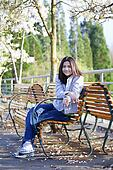 Young teen girl sitting on bench under cherry blossom tree
