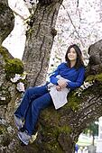 Young teen girl sitting in cherry tree in full bloom