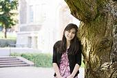 Teen girl leaning against trunk of large tree, smiling