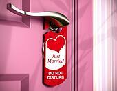 just married written onto a red door hanger, hanged on a metal handle of a pink bedroom door, concept of honeymoon.