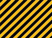 Yellow and black diagonal hazard stripes painted on old brick wa
