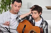 Man teaching to boy how to play guitar