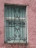 black metal forged carved lattice at a  white window