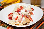 Crepes with strawberry, banana and whip cream