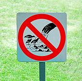 The sign of no feeding bird and fish on green grass background