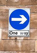 One way sign on a stone wall