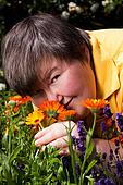 disabled woman lying on grass and smell of flowers