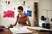 hispanic woman doing budget in fashion designer atelier