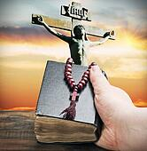 hand holds the bible on the background of the Crucifixion of Jesus Chris
