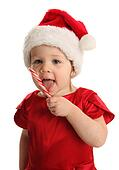 Child eating a candy cane wearing a santa hat