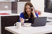 Woman multitasking over breakfast