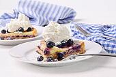 Blueberry lemon tart with whip cream on wood table