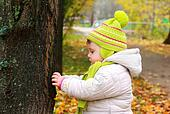 Thinking baby looking on big tree and touching on autumn yellow