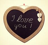 Wooden board for notes in a heart shape with the words white chalk I love you