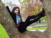 Smiling beautiful woman sitting on big trunk tree on autumn back