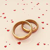 Golden wedding rings on beige background with red hearts