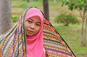 Close-up portrait of beautiful Muslim girl gazing steadily at the camera outdoors