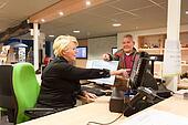 Senior volunteer woman selling museum ticket