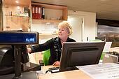 Senior volunteer female cashier at museum