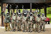 Boys dressed in camouflage stand in a row on a paintball base, r