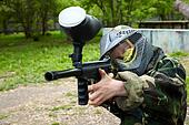 Paintball player in camouflage uniform and protective mask with traces of paintbal hit aims with marker into enemies.